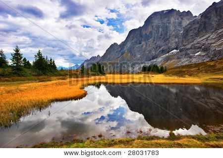 Small fine and smooth lake in the Swiss Alps, reflecting mountains