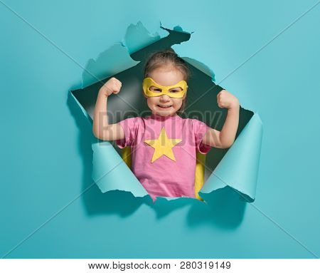 Little child playing superhero. Kid on the background of bright blue wall. Girl power concept. Yellow, pink and  turquoise colors.