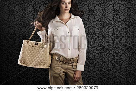 Elegant woman in silk  blouse  and dark beige trousers holding leather bag.
