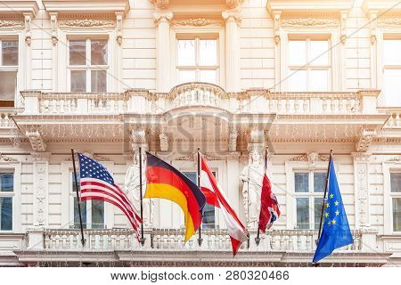 National Flags On Old Building Facade In European City. Flags Of Usa, Germany, Austria, European Uni