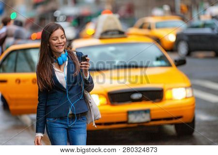 Young woman walking in New York city using phone app for taxi ride hailing with headphones commuting from work. Asian girl happy texting on smartphone. Urban walk commuter NYC.