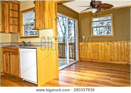 Home Interior Showing Kitchen Area,den,and Sliding Glass Doors Leading To A Back Deck.
