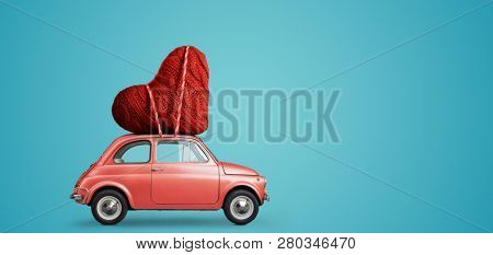 Living coral retro toy car delivering craft heart for Valentine's day on blue background