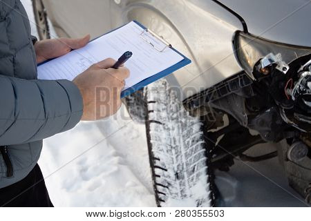 Insurance Agent Checking Car After Car Accident And Filling Accident Details Form. Winter Time. Focu