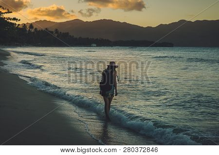 Traveler Girl Walking On Tropical Beach In Sunset.vintage Photo Of Young Girl Traveler In Vacation.