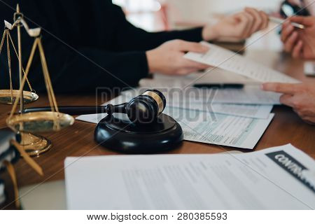Business Man And Team And Lawyers Discussing Contract Papers With Brass Scale On Wooden Desk In Offi