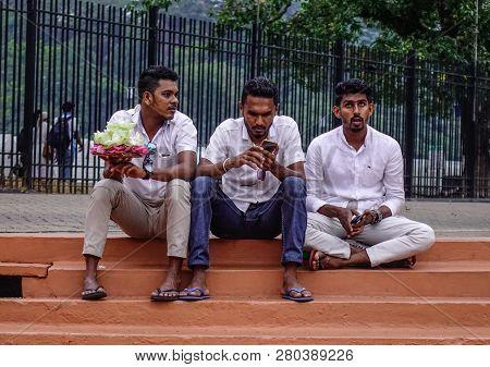 Kandy, Sri Lanka - Dec 15, 2018. Local Young Men Sitting At Temple Of The Sacred Tooth Relic In Kand