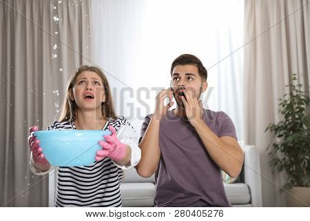 Emotional Young Woman Collecting Water Leaking From Ceiling While Her Husband Calling Plumber In Liv