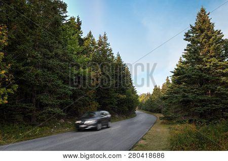 Car Speeds Around Curve In Acadia National Park - Mt Desert Island, Maine, Usa