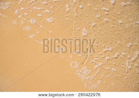Foamy Sea Water Over Yellow Sand Beach. Tropical Seaside Concept Photo. Seawater On Sand Beach. Seas