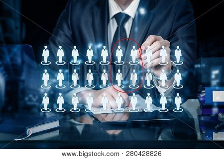 A Businessman Is Sitting At The Table And Operating With Management Structure Of Human Figures Icons