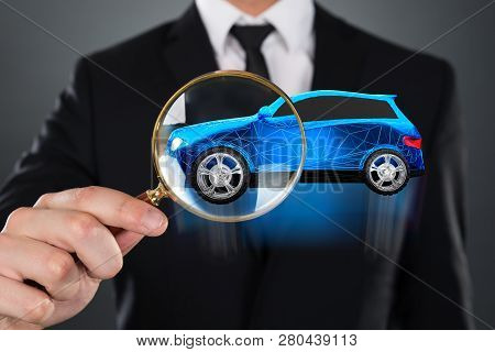 Blue Car With Polygonal Pattern Seen Through Businessperson Holding Magnifying Glass