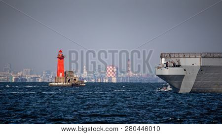 A Navy Warship Approaches The Lighthouse In Yokosuka, Japan.