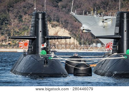 Two Japanese Submarines Flying Their Flags And Moored At A Dock In Eastern Japan.
