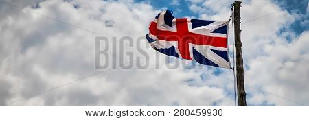 A British Union Jack, Probably 16th Century Replica, Flying With Clouds In The Background.