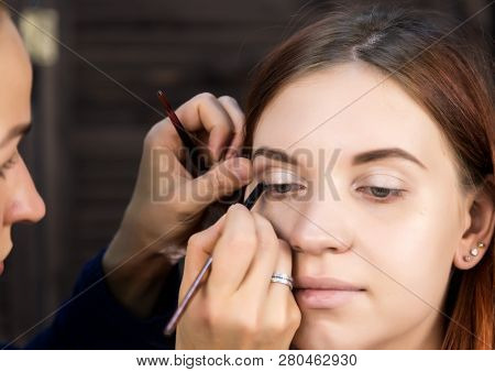 Makeup Artist Preparing Young Beautiful Woman. Close-up Eyeliner
