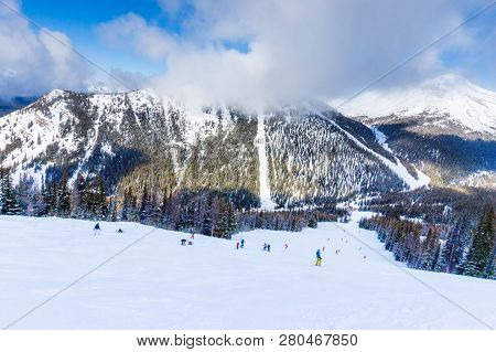 Unidentifiable Skiers And Snowboarders At A Distance Going Down A Mountain Slope In Lake Louise In T