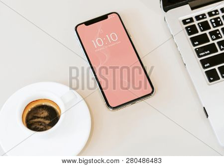 Phone mockup on white table with a laptop and a coffee cup