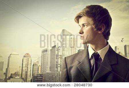 Profile of a young businessman with cityscape in the background