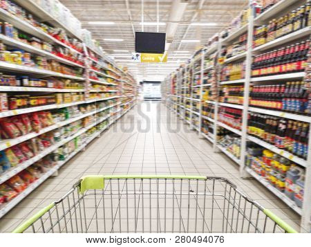 Shopping Cart With Abstract Blurred Supermarket Aisle With Colorful Goods On Shelves At Background,