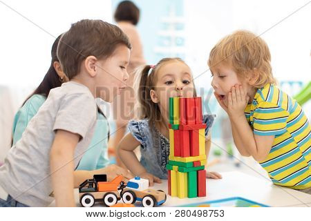 Little Kids Build Wooden Toys At Home Or Daycare. Emotional Kids Playing With Color Blocks. Educatio