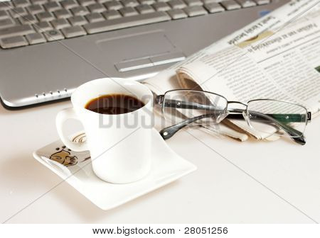 Coffee cup with laptop, glasses and newspaper