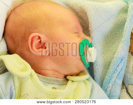 Closeup Of Little Newborn Sleeping With Teat In Mouth