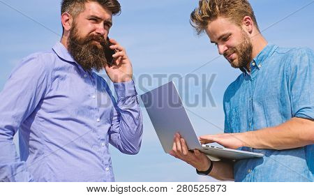 Business Team Works Outdoor, Sky Background. Men With Laptop And Smartphone Solving Problems Using M