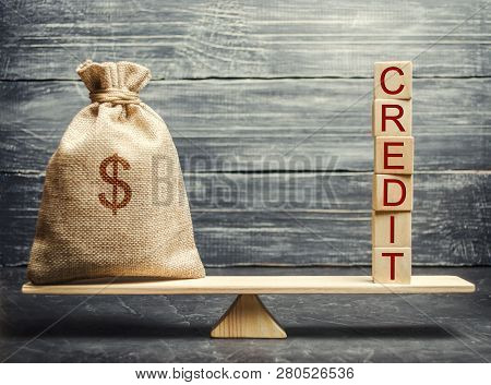 Money Bag And Wooden Blocks With The Word Credit On The Scales. The Concept Of A Successful Loan. Co