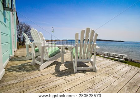 Deck With A View. Wood Deck With View Of Water And White Adirondack Patio Chairs For Outdoor Seating