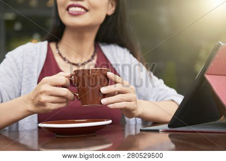 Close-up Of Smiling Young Lady Sitting At The Table With Touchpad In Front Of Her And Holding Cup Of