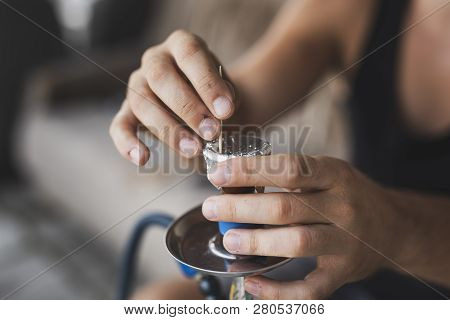 Detail of male hands punching holes in tinfoil placed over a fruity flavored, molasses based hokkah tobacco using a toothpick, getting it ready for use. Selective focus on the fingers poster