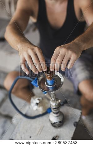 Man filling up the hookah with fruity flavored, molasses based eastern tobacco, getting it ready for use. poster