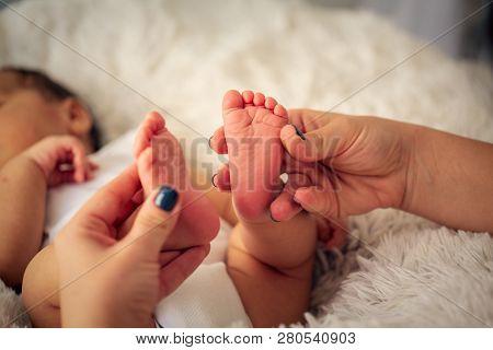 Beautiful Infant Baby Feet In Mother Palm. Feet Of Little Baby Boy, Newborn Baby Foot, Newborn Baby