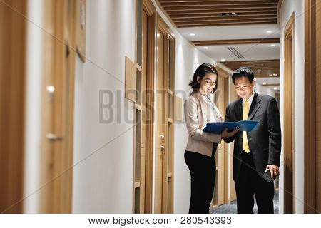 Businesswoman Explaining Documents To Happy Chinese Client In Bank Office