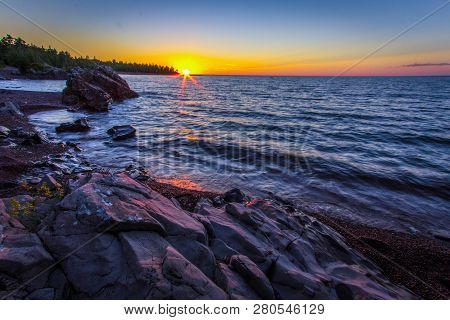 Rocky Coastal Sunset Landscape. Sunset Over The Horizon Of Lake Superior With A Rocky Coastline In T