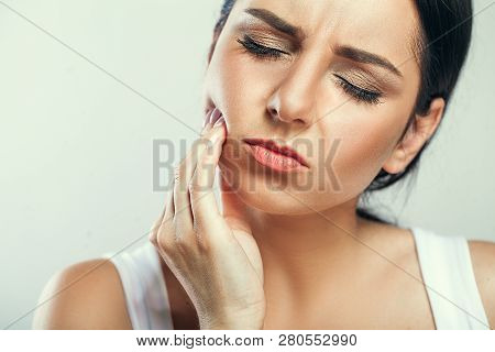Tooth Pain And Dentistry. Beautiful Young Woman Suffering From Terrible Strong Teeth Pain, Touching