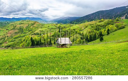 Hay Shed On A Grassy Field In Mountains. Beautiful Countryside Landscape In Springtime. Cloudy Foren