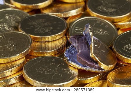 Chocolate Money Pile Of Gold Coins. Edible Sweets Covered In Foil As Pretend Money. One Open Coin Ha