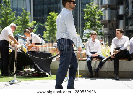 London, Uk - 26 June, 2018: Young Man Walking Next To Office Workers Who Having Lunch In The Bank Pa