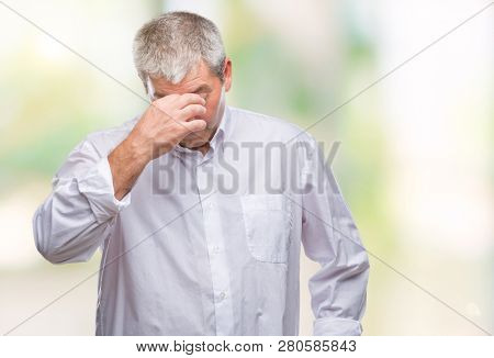 Handsome senior man over isolated background tired rubbing nose and eyes feeling fatigue and headache. Stress and frustration concept.