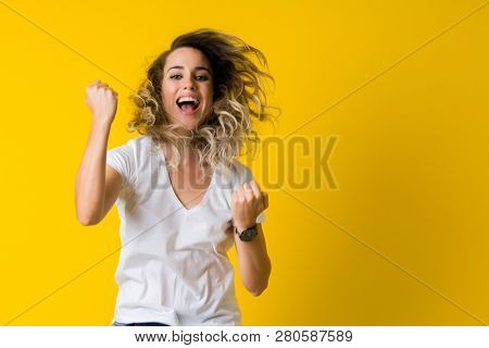Beautiful young blonde woman jumping happy and celebrating with raised hands and open mouth over isolated yellow background