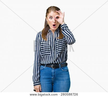 Middle age mature business woman over isolated background doing ok gesture shocked with surprised face, eye looking through fingers. Unbelieving expression.