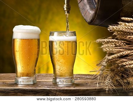 Pouring into beer glass. Glasses of beer and cask on the wooden table. Craft brewery.