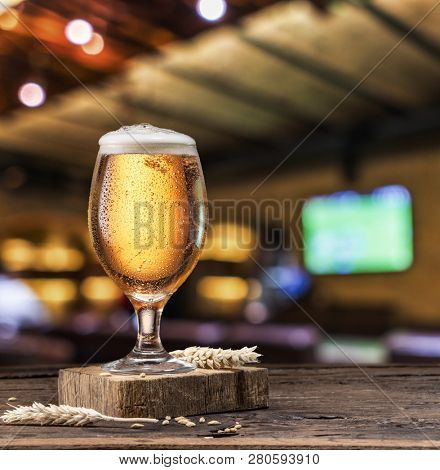 Chilled glass of light beer on old wooden table. Blurred bar background.