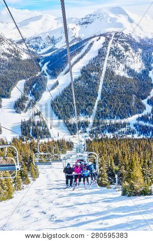 Unidentifiable Skiers On Chairlift Going Up A Ski Slope In The Snowy Mountain Range Of The Canadian
