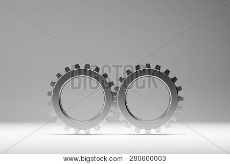 Two Metal Gears Over Gray Background. Concept Of Cooperation And Teamwork In Business. 3d Rendering.