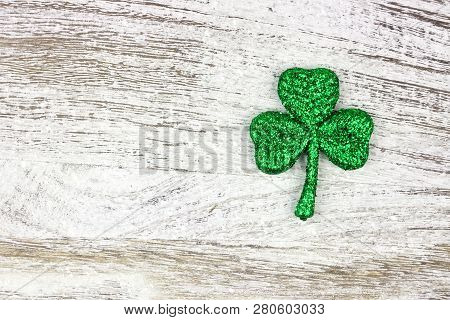 Single St Patricks Day Glittery Shamrock Over An Old Rustic White Wood Background