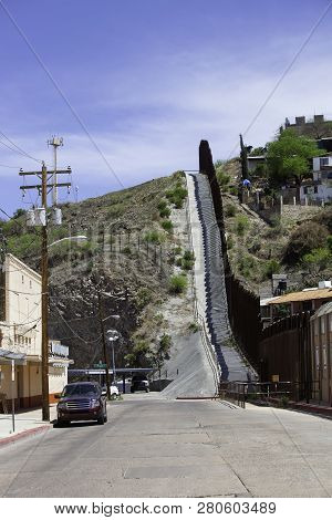 United States Border Wall With Nogales Mexico On The Right And Surveillance Tower On The Left