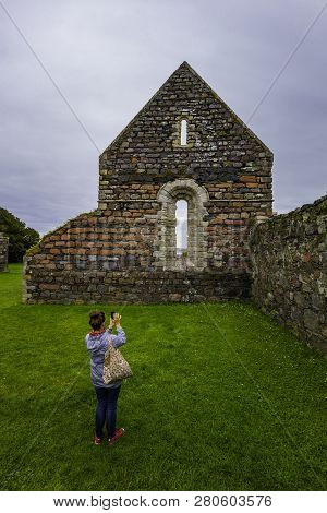Woman Photographs The Ruins Of The Nunnery On The Island Of Iona